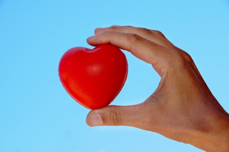 a hand holding a red heart over the sky photo