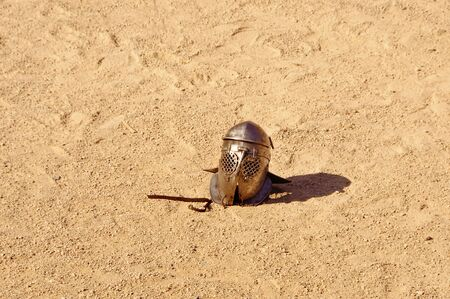 gladiator: a helmet lying on the ground after a fight of gladiators Stock Photo