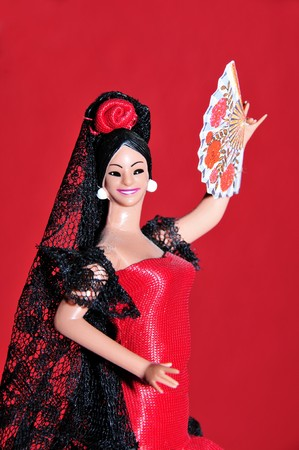fandango: a typical spanish doll dressed as a flamenca isolated on a RED background
