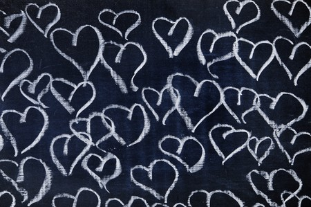 several hearts drawn with a chalk on a blackboard photo