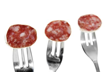 llonganissa: spanish salami slices in forks  isolated on a white background
