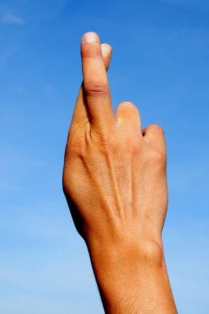dedo           �       �ndice: una mano de hombre cruzar dos dedos en el cielo  Foto de archivo