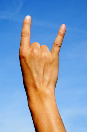 a man hand making the sign of the horns over the sky photo