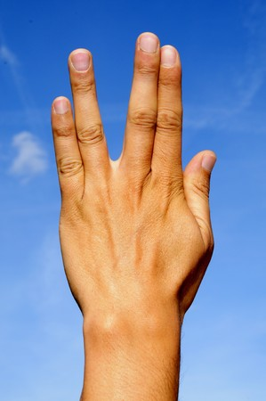 a man hand doing the trekkie gesture over the blue sky photo