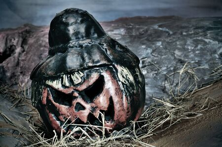 closeup of a jack-o-lantern in a cemetery for Halloween photo