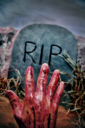 grave stone: closeup of a grave with a bloody hand in a cemetery for Halloween Stock Photo