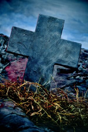 closeup of a stone cross in a grave in a cemetery for Halloween photo