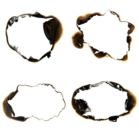 paper hole: burned holes on a white paper background Stock Photo