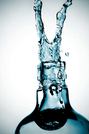 splash water out of a glass bottle photo