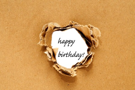 Happy birthday written on a hole on a brown cardboard background Stock Photo - 8110757
