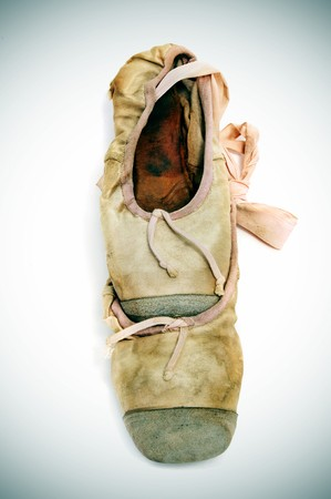 vignetted: a pair of old pointe shoes isolated on a vignetted background