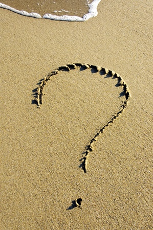 suspense: a question mark drawn on the sand of a beach