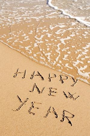 sentencia: Feliz a�o nuevo de frase escrita en la arena de una playa Foto de archivo