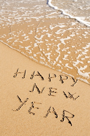 sentence happy new year written in the sand of a beach photo