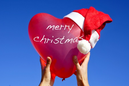 merry christmas written in a heart-shaped balloon with a santa hat photo