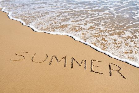 verano: verano de la palabra escrita en la arena de una playa
