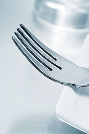 a dinner set formed by a plate, a fork and a glass photo