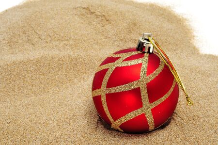 a red and golden christmas ball on the sand photo