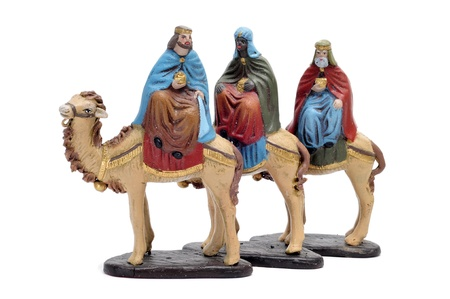 figures representing the three kings in a nativity scene on white background photo