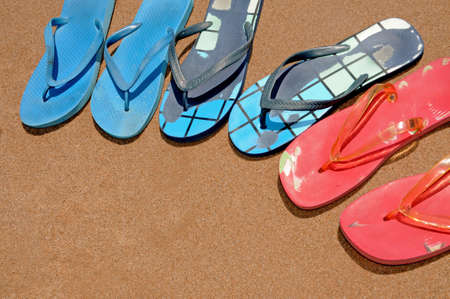 a pile of flip-flops on the sand of a beach photo