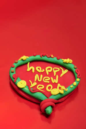 modelling: happy new year written in a design made with modelling clay on a red background