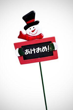 broaching: happy new year written in japanese in a blackboard label with a snowman