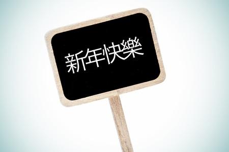 broaching: happy new year written in chinese a blackboard label Stock Photo