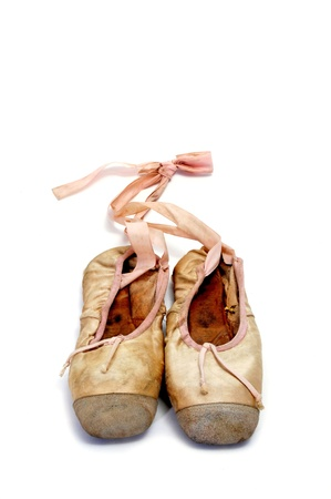 decadence: a pair of old pointe shoes isolated on a white background Stock Photo