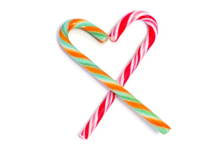 hard love: two candy canes forming a heart isolated on a white background