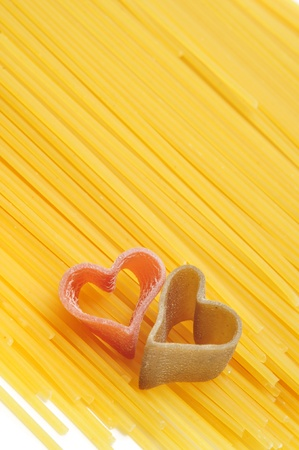 heart shaped pasta on a spaghetti background photo