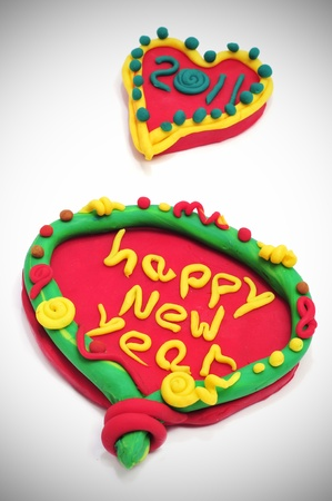happy new year 2011 in a design made with modelling clay on a white background photo