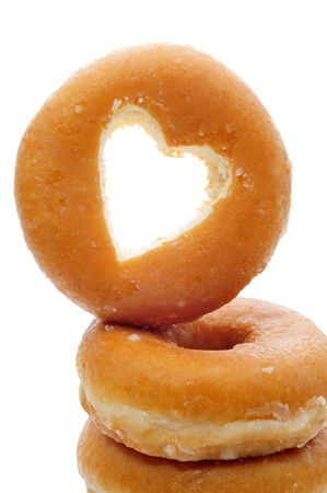 a pile of donuts one with the hole shaped as a heart on a white background photo