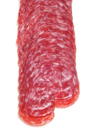 llonganissa: a pile of sliced fuet, spanish salami, isolated on a white background