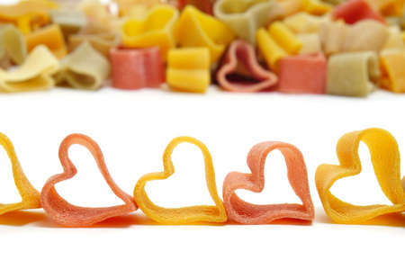 a pile of uncooked vegetables heart shaped pasta photo