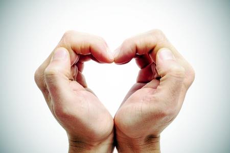 paliza: hombre manos formando un coraz�n en un fondo vignetted Foto de archivo