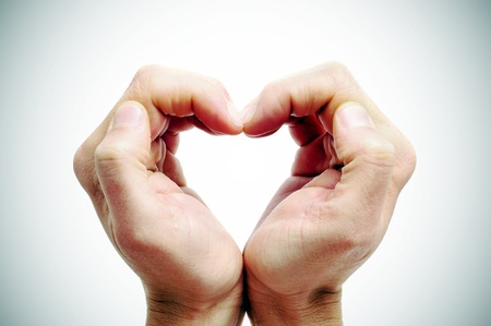 vignetted: man hands forming a heart on a vignetted background Stock Photo