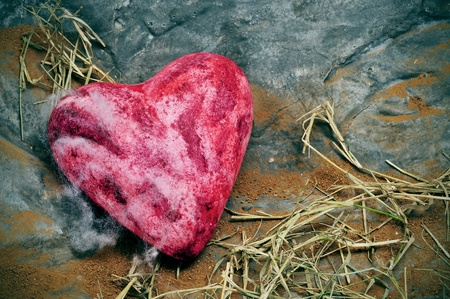 decadence: red heart in a gray rock background
