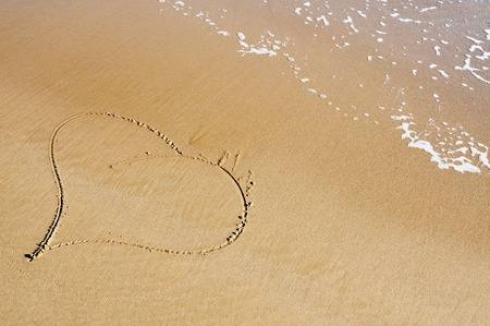 evoking: a heart drawn on the sand of a beach