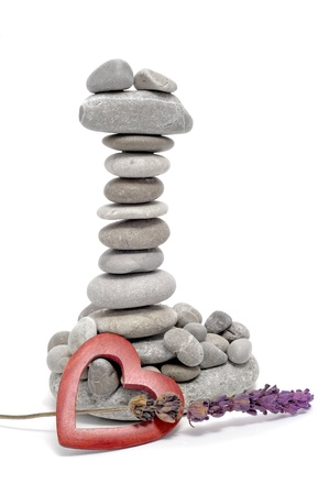 a pile of zen stones with a wooden heart and lavender on a white background photo