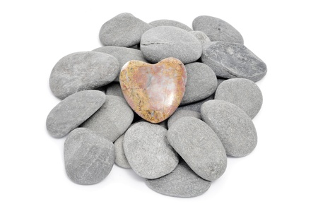 a pile of stones, one heart shapped, on a white background photo