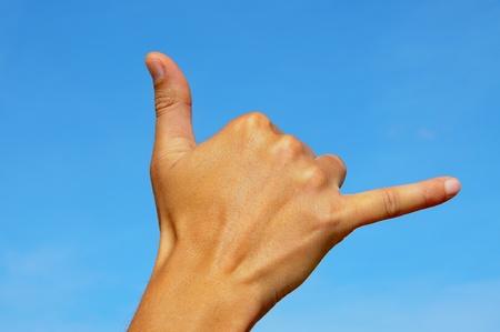 una mano de hombre haciendo el signo de shaka
