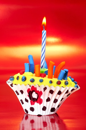 a birthday cupcake on a red background Stock Photo - 8781443