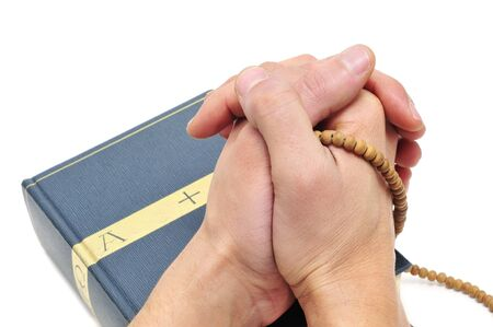 someone praying on a bible with a rosary photo