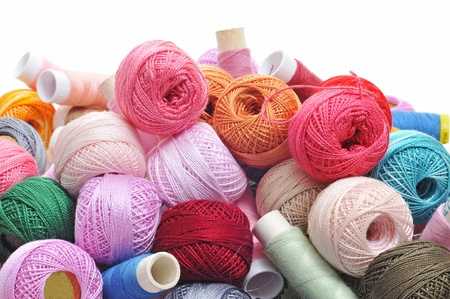spools and balls of yarn of many colors on a white background photo