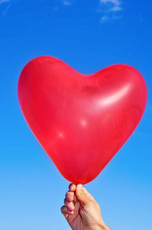someone holding a heart-shaped balloon over the sky photo