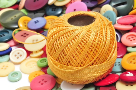 a spool of thread and buttons of many colors on a white background photo