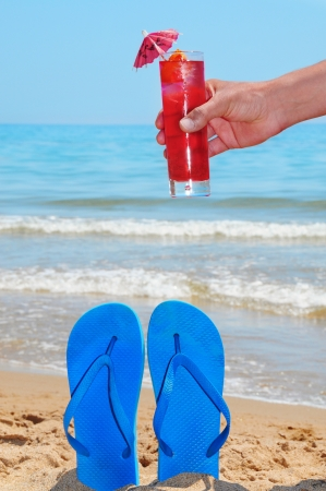 someone holding a cocktail  and a pair of flip-flops and on the beach photo