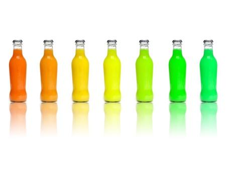 vitamina a: algunas botellas de jugo de diferentes colores sobre un fondo blanco  Foto de archivo