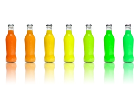 green glass bottle: some juice bottles of different colors on a white background