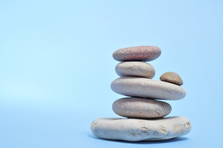 a pile of zen stones on a blue background photo